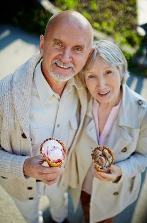 elderly adults: Seniors with ice-cream looking at camera Stock Photo