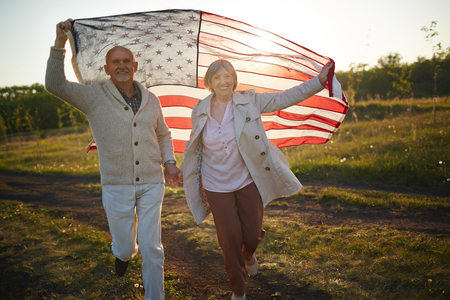 Seniors with American flag running down green field Фото со стока
