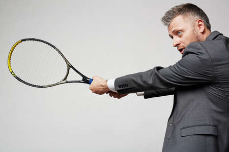business rival: Experienced employee with tennis racket defending from attack of business rival