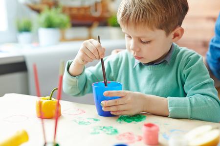 peer to peer: Little boy painting peer with gouache to make prints