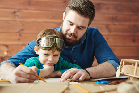 selfmade: Man drwaing sketch of self-made toy with his son near by Stock Photo