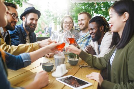intercultural: Happy intercultural friendly young people toasting with drinks in summer cafe Stock Photo
