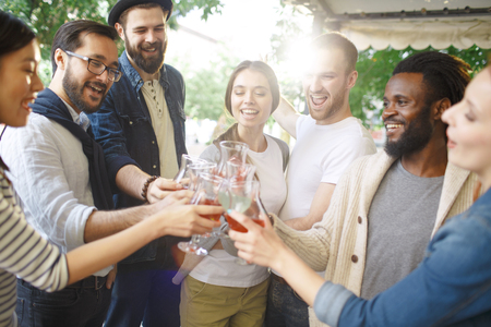 Group of ecstatic friends cheering up with cocktails