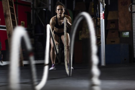 activewear: Active young woman in activewear working out with ropes