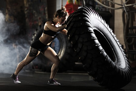 Strong fit woman flipping tire in gym