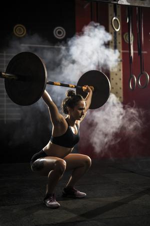 effort: Pretty woman in sportswear lifting weight Stock Photo