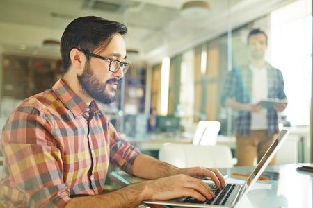 trabajo oficina: joven empresario a escribir en la computadora portátil en lugar de trabajo Foto de archivo