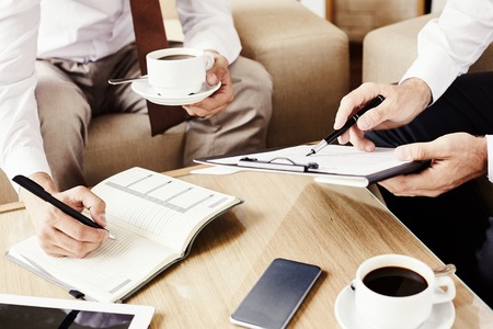 tomando café: La gente de negocios utilizando un teléfono inteligente en un café
