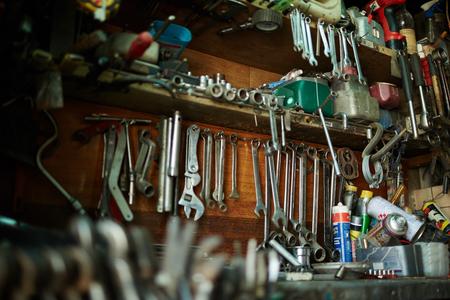 herramientas de mecánica: herramientas antiguas que cuelgan en la pared en el taller