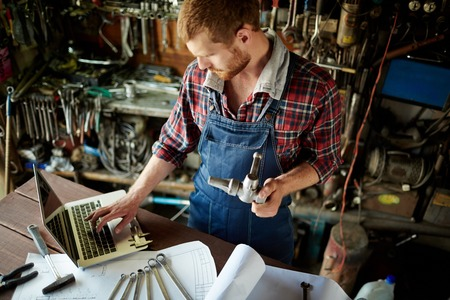 Auto mecánico usando el ordenador portátil en su taller