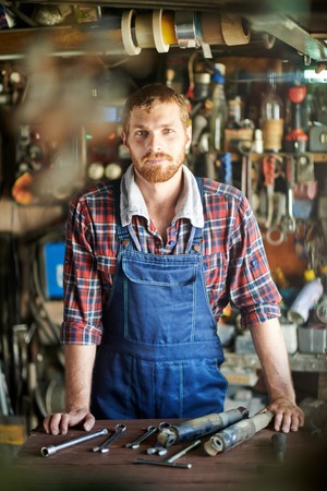 work table: Portrait of attractive young mechanic wearing overalls