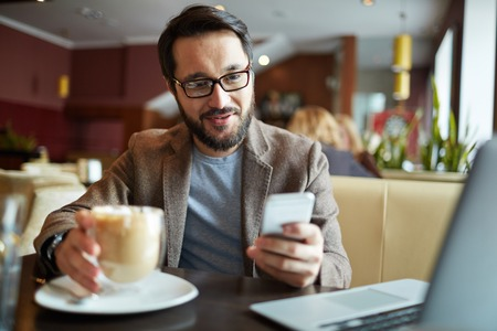 asian business man: Young businessman in eyeglasses drinking coffee and using his smartphone Stock Photo
