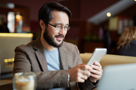 one young man: Man wearing his eyeglasses using smartphone