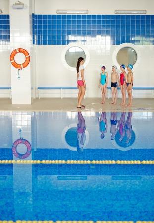 explaining: Teacher explaining active kids rules of swimming Stock Photo