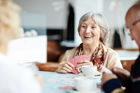 Happy senior woman playing cards with friends in cafe