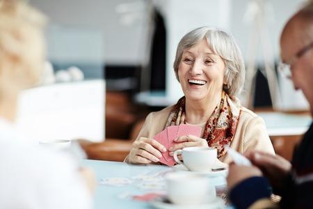 ancianos felices: Mujer mayor feliz jugando a las cartas con sus amigos en el café