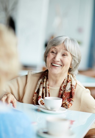 happy seniors: Cheerful senior woman talking to her friend by cup of tea