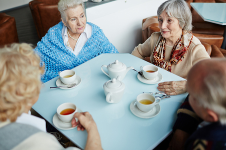 senior group: Four eldlerly people talking while sitting by table in cafe Stock Photo