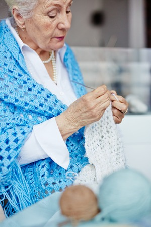 Granny knitting white woolen scarf