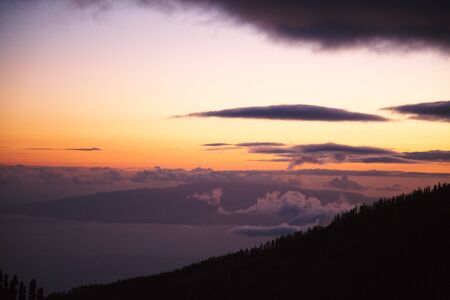 mountain sunset: Cloudscape over hill or mountain covered with trees Stock Photo