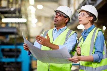 assistant engineer: Mature engineer showing his assistant new machine or detail