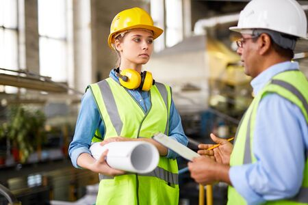 executive helmet: Attractive girl with blueprint talking to co-worker