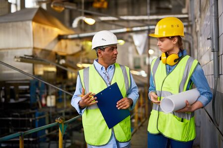 executive helmet: Two modern engineers discussing work at plant Stock Photo