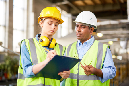 executive helmet: Engineer making notes on clipboard while listening to foreman Stock Photo
