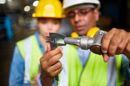 assistant engineer: Engineer with metallic machine part measuring and showing it to his assistant Stock Photo
