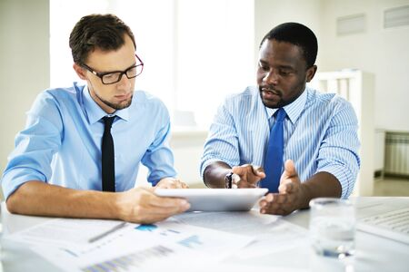 Serious businessmen looking at touchpad screen with data Stock Photo