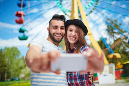 Happy couple making selfie in amusement park Stock Photo