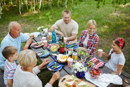 grandkid: Family of six gathered around table in natural environment