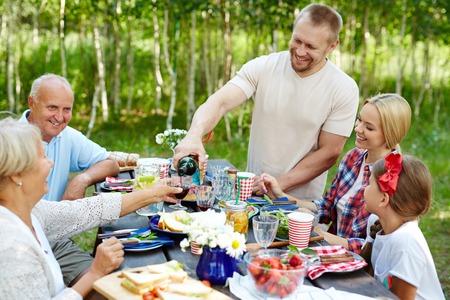 familias jovenes: Gran familia sentada alrededor de la mesa y cenar en el ambiente natural