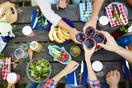 Hands with red wine toasting over served table with food Stockfoto