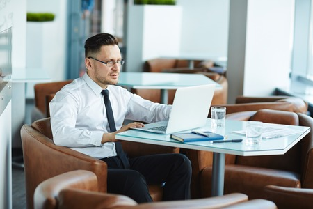 work addicted: Young businessman sitting in cafe in front of laptop Stock Photo