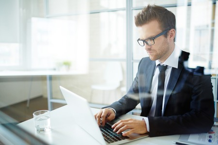 success man: Handsome employee typing at workplace Stock Photo