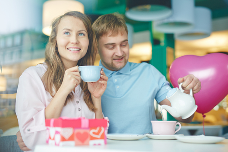 Amorous couple sitting in cafe and having tea