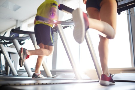 Active young woman running on treadmill in gym photo