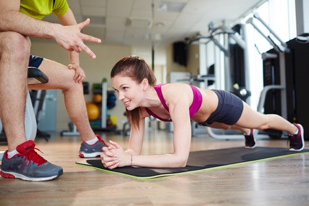 Fit young woman doing planks on mat photo