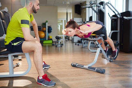 Fit girl doing push-ups on special sportive equipment photo
