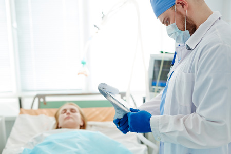 Doctor in mask and uniform reading medical document by bed of patient