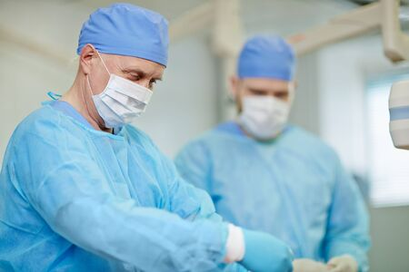 operational: Surgeons in mask and protective uniform working in operational room Stock Photo