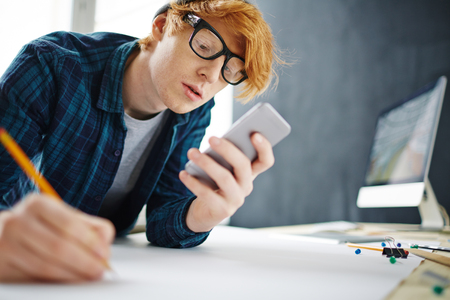 artistic addiction: Young man writing sms during work