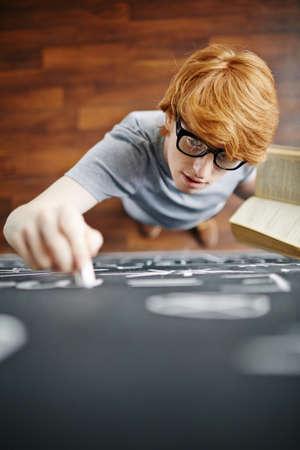 hombre escribiendo: Estudiante con la escritura del libro en la pizarra con tiza Foto de archivo