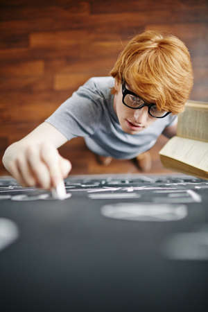 man writing: Student with book writing on blackboard with chalk