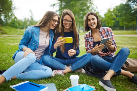 people laughing: Girls with gadgets spending time in park