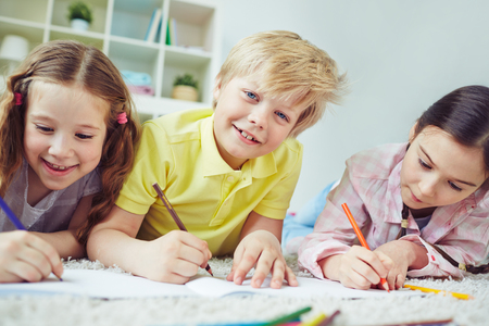 three children: Three children drawing together while lying on the floor