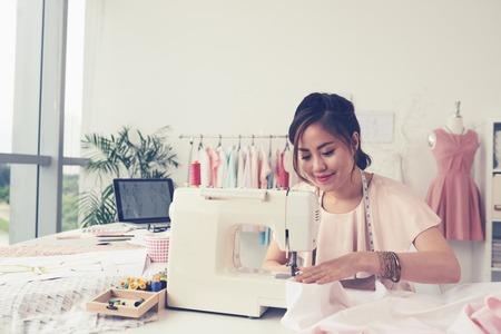 Diseñador de moda sonriente que usa la máquina de coser y se sienta detrás de su escritorio Foto de archivo