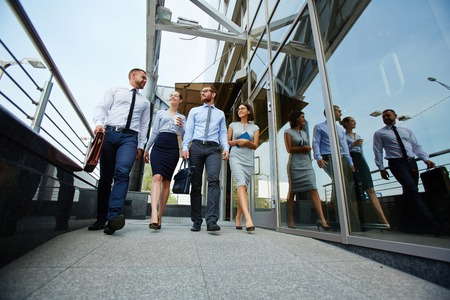 executive women: Team of colleagues moving along glass wall
