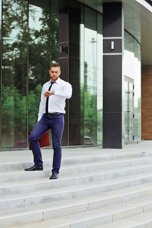 haste: Businessman checking time by office center Stock Photo